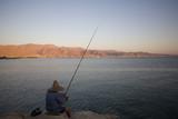Fisherman off pier in Eilat fishing towards Aqaba Jordan poster