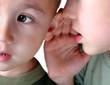 Один ребенок шепчет что-то другому на ухо.  Нажмите для увеличения.