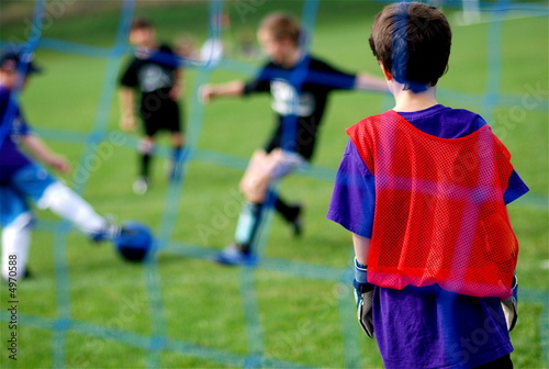 Young Goalie watching Kids Kick the Soccer Ball in front of Net