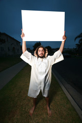 Crazy looking man holds a big blank poster sign at night