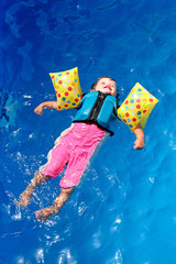 Girl toddler floating on top of swimming pool