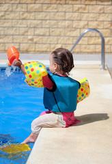 Girl toddler sitting next to swimming pool