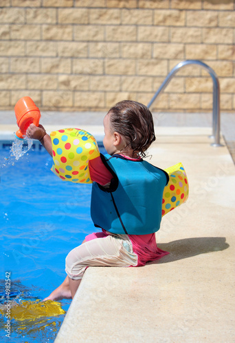 Girl toddler sitting next to swimming pool