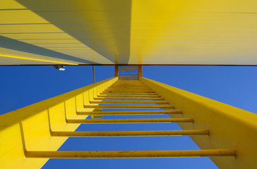 Yellow ladder, stairway up to the blue sky