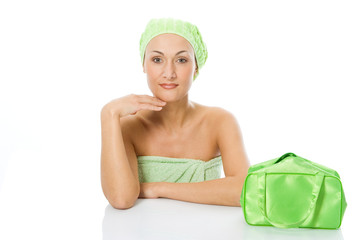 beauty spa woman in green towel with bag sit on the table
