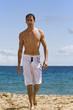 jeune homme séduisant debout marche sur la plage au soleil