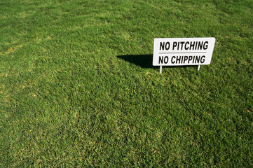 No Pitching, No Chipping sign in Lush Green Golf Course Grass.