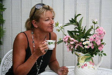 Swedish woman is taking a pause in garden with a cup of coffee