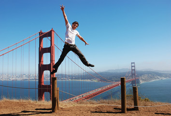 Happy young man jumping high next to the Golden Gate bridge