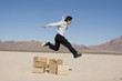 Businesman jumping over boxes