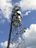 top of antenna mast under sky with clouds poster