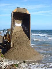 A truck off-loading sand on a spanish beach