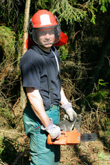 Smiling forestry worker with a chainsaw
