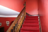 staircase. red staircase with wooden bannister or handrail poster