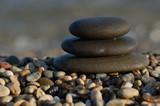 three balanced rocks contrast a sea of stones poster