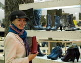 Beautiful girl in a shop buying winter boots poster