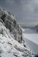 High mountain slope. Rock, snow and sky.