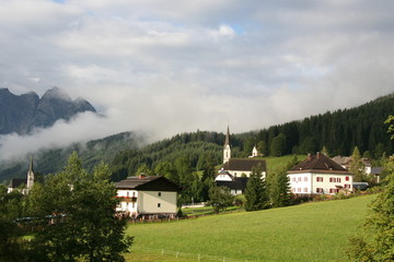 Meadow in the high mountains with houses, trees and church