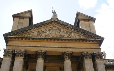 roof. portico with coat of arms & statue on top of columns