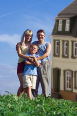 family mother father and child against a background house
