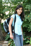Pretty teen girl standing with backpack outdoors poster