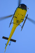 Yellow helicopter in blue sky