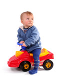 little blond boy driving a red toy car