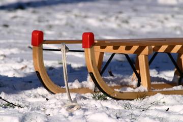 Schlitten steht im Schnee, Rasen scheint durch