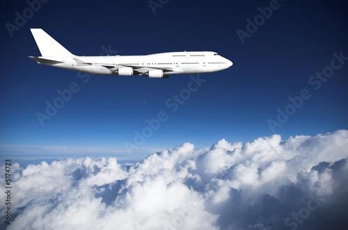 Papiers peints Avion à Moteur Jumbo jet above clouds