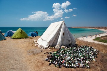 Camping on sea coast. Tent and bottles garbage.