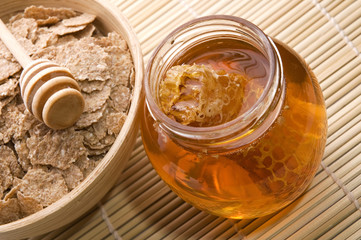 fresh honey with honeycomb and breakfast flakes