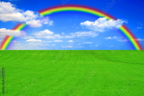 Green grass with blue cloudy sky and rainbow