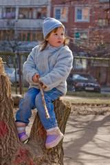 Kid sitting on stump