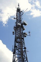 top of antenna mast under sky with clouds