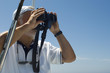 Captain of Racing Yacht Using Binoculars