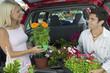 Couple Loading Plants Into Minivan