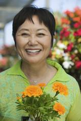 Woman Holding Flowers in plant nursery, portrait