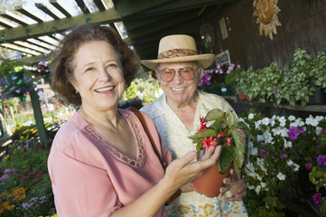 Senior Couple Shopping for flowers at plant nursery, portrait
