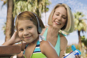 Grandmother applying sunscreen to girl 7-9 listening to headphones, portrait.