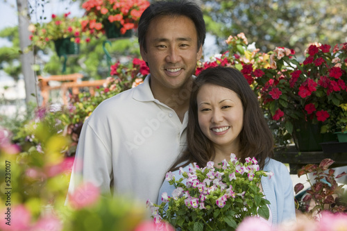 Couple holding plants in plant nursery, portrait