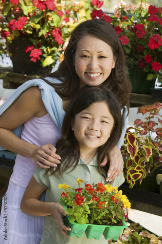Mother with daughter holding young flowers in plant nursery, portrait