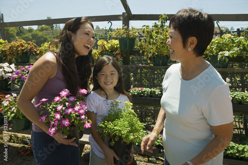 Mother, daughter and grandmother shopping in plant nursery