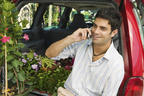 Man sitting by flowers on back of minivan using cell phone