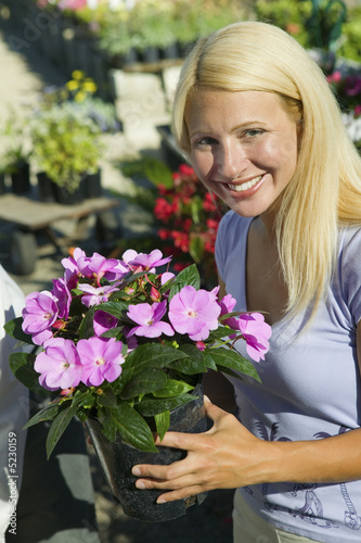 Woman Holding Flowers in plant nursery, portrait