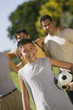 Boy 13-15 holding soccer ball, with three men in park.