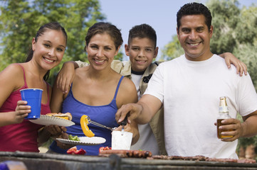 Boy 13-15 with family at outdoor grill, front view.