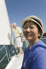 Woman smiling on sailboat, husband in background, portrait