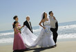 Bride and Groom walking with family on beach