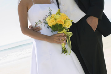 Bride and Groom with bouquet on beach, close-up