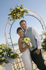 Bride and Groom under archway on beach, portrait